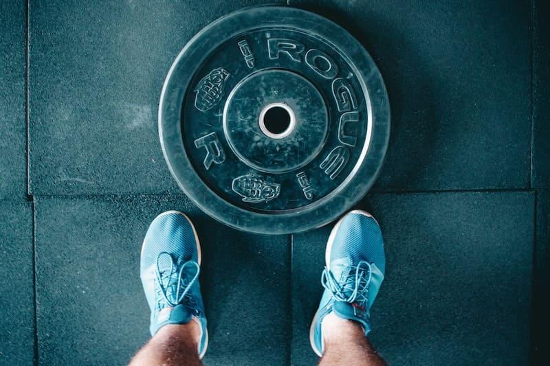 Piernas junto a un disco de pesas